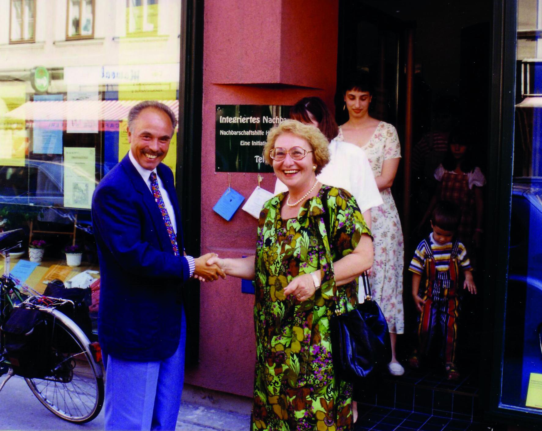 Ein Mann und eine Frau geben sich vor dem Nachbarschaftszentrum 17 die Hand